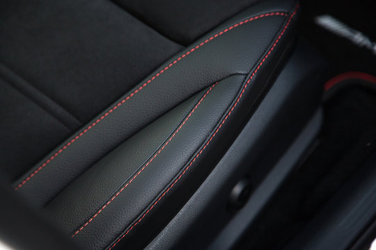 Red stitching on black leather car seat