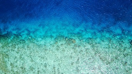 P02664 Aerial flying drone view of Maldives white sandy beach abstract waves water surface texture on sunny tropical paradise island with aqua blue sky sea ocean 4k