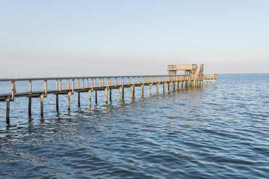 Wooden fishing piers stretching out over Galveston Bay in Kemah, Texas, USA. Foot pier for saltwater fishing of vacation home/beach house rental/bay home in Lighthouse District waterfront at sunset