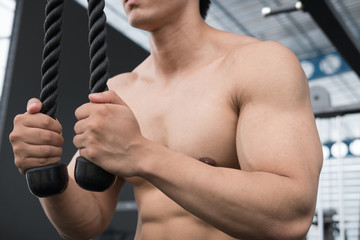 young man execute exercise with weightlifting machine in fitness center. male athlete pump up muscle with pull down machine in gym. sporty guy working out in health club.