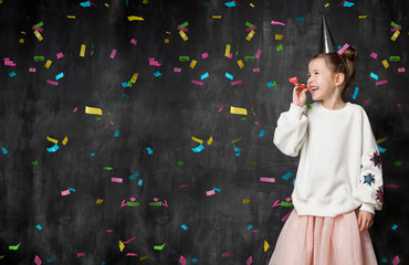 Little girl laughs and has fun at a celebration on the background of a school board and confetti with a free place on the left