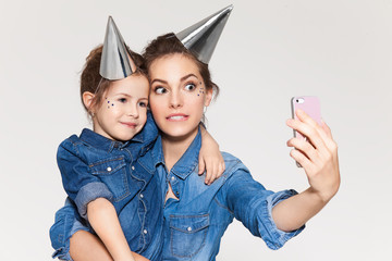 Beautiful mother with daughter dressed equally photographed on the phone in holiday caps on a white background