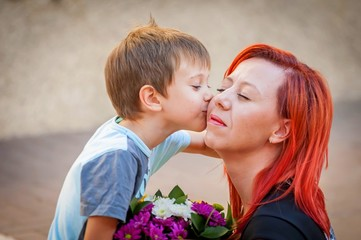 Little cute baby son kissing his mother. Mother's Day illustrative stock image.