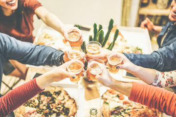 Group of friends enjoying dinner toasting with beers and eating pizza at home