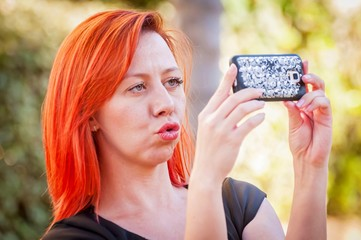 Young and attractive Caucasian girl holding the cellular phone in her hands and making a self portrait. Beautiful girl with duck face stock image.