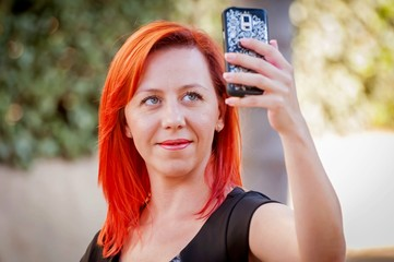 Young and attractive Caucasian girl in her 30s holding the cellular phone in her hands and making a self portrait.