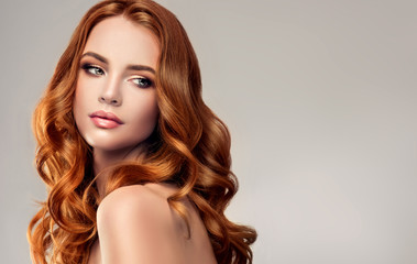 Beautiful model girl with long red curly hair .Red head . Care and beauty hair products   Wall mural