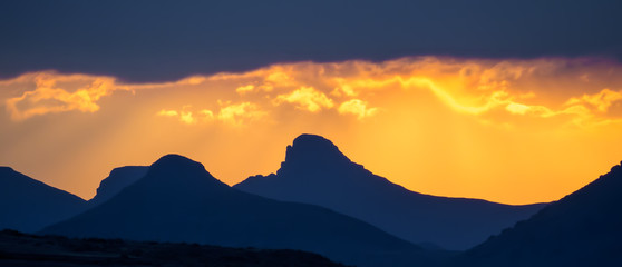 Dramatic yellow orange sunset over mountains with storm clouds, Lesotho, Southern Africa