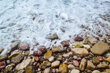 Sea waves, sea foam, break up on the coastal stones.