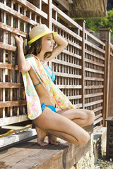 Summer outdoor portrait of attractive woman in poreo and swimsuit against wooden fence