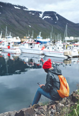 photo of girl in warm clothing with backpack on pier with background of mountains of West Fjords, Iceland. woman takes a photo on smartphone