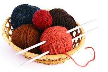 Set for knitting, knitting needles and multi-colored skeins of wool in a wicker basket on a white background.