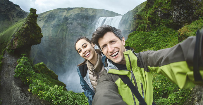 smiling couple, man and woman in warm clothes making selfie on a Skogafoss waterfall background, Iceland. Focus on the man