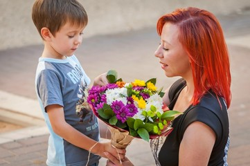 Cute Caucasian boy handing a flower bouquet to his mother. Mother's day illustration.
