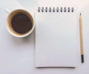 A notebook, a pencil, a Cup of coffee on a white background. Top view