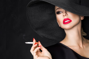 Elegant woman, femme fatale in black hat with cigarette in hand. On black background Wall mural