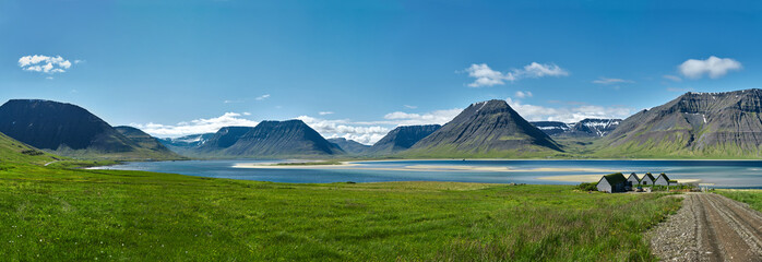 Canvas Prints Blue jeans Travel to Iceland. beautiful sunrise over the ocean and fjord in Iceland. Icelandic landscape with mountains, blue sky and green grass on the foreground. View of the road to houses in the north-west