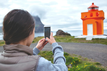 Woman taking photo of lighthouse in vacation in Iceland
