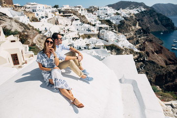 The couple is sitting on the roof in Santorini, hugging and laughing