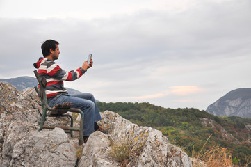 Man with phone on cliff taking photo. Man sitting on edge of the cliff and work on mobile