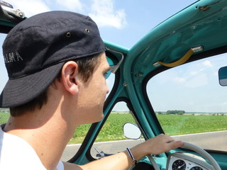 Young man driving heinkel cabin (vintage car) in turquoise 1