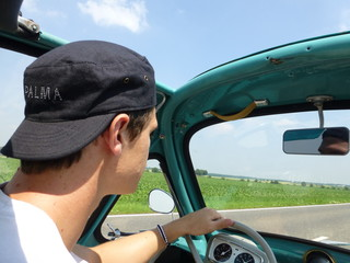 Young man driving heinkel cabin (vintage car) in turquoise 3