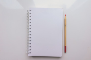 Open Notepad with a blank sheet of paper and a pencil on a white background. Top view