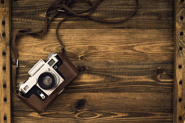 Old retro camera on vintage rustic wooden planks boards. Education photography courses back to  school concept abstract background. Close up, top view, copy space.