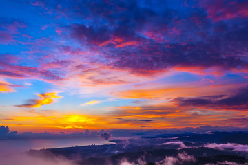 Incredible colorful sunset on the seashore, hills and mountains under clouds of different colors. Big Sochi, Russia.
