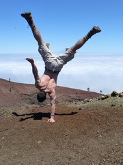 One-armed handstand on the top of the volcano San Martin on the island of La Palma, one of the Canary Islands
