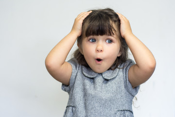 Surprised or shocked face of four years old pretty brunette caucasian child girl. Shock - facial expression. Layout with free copy space.
