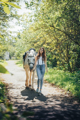 Girl teenager and white horse in a park in a summer