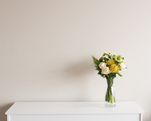 Yellow and cream flowers in glass vase on white sideboard against neutral wall background with copy space to left