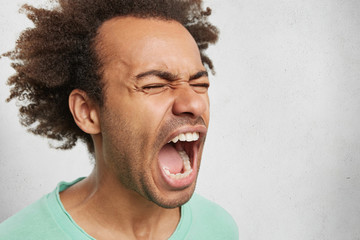Close up portrait of mad angry young dark skinned male screams in anger and fury, being fed up with everything, has stressful situation in life, isolated over white background. Man shouts loudly