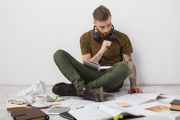Concentrated hipster guy with tattooes, sits crossed legs on floor, reads books and writes notes, being busy with studying or making project, has no spare time, prepares for session. Working concept