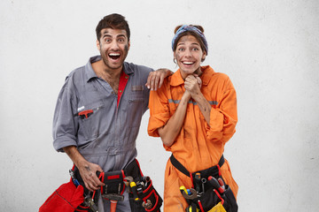 Indoor picture of emotional female and male plumbers being excited as promoted at work, recieve award from boss. Happy successful professional industrial workers rejoice coming weekends and rest