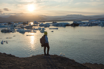 Back view of traveler young men standing. Glacier lagoon Jokulsarlon, Iceland