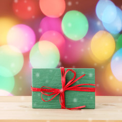 Christmas, new year gift box on wood table over blur festive bokeh light background, with copy space for greeting text, greeting card banner