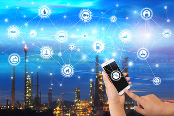 Industry 4.0 connect hand holding smartphone and industrial icons on oil refinery industry sunset background.