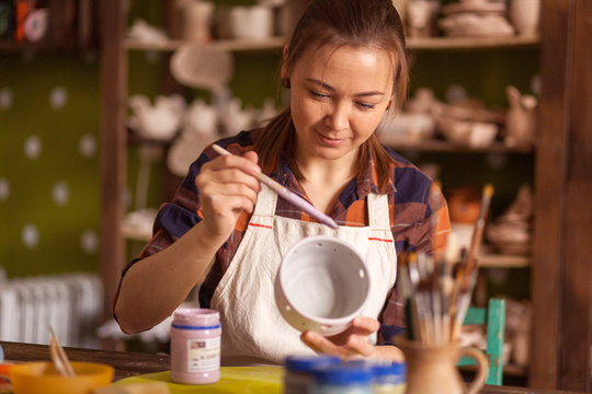 A dark-haired young woman, a potter in a plaid shirt and apron, paints a clay cup in a gray color on a wooden table, on which there are tools, and in the background in the workshop clay vases
