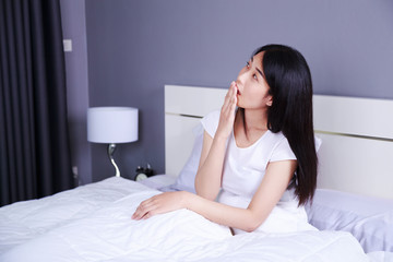 sleepy woman yawning on bed in the bedroom