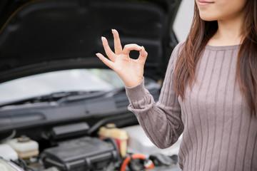 車のエンジンルームと女性
