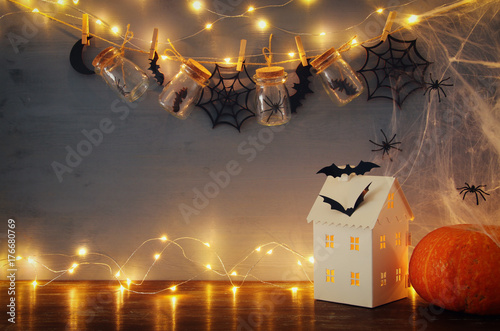 Halloween holiday concept. Mysterious house with lights in front of masson jars with spiders and baths