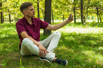 Young man is taking selfie photo with smartphone at the summer park