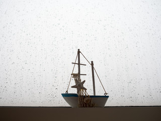 Boat model with rain drops on windows glass.