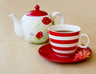 striped cup with tea on a saucer and brewer with a poppy picture on a wooden table top and red rose flower