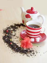 striped cup with tea on a saucer pieces of sugar cubes, semicircular spice, small wild strawberries and brewer with a poppy picture on a wooden table top, red flower