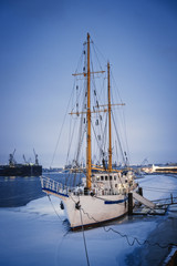 Sailing ship on the dock/Masted ship on the quay on the Neva river in winter, St. Petersburg, Russia