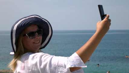 Happy woman in hat , making a selfie on the beach taking photographs with a smartphone.