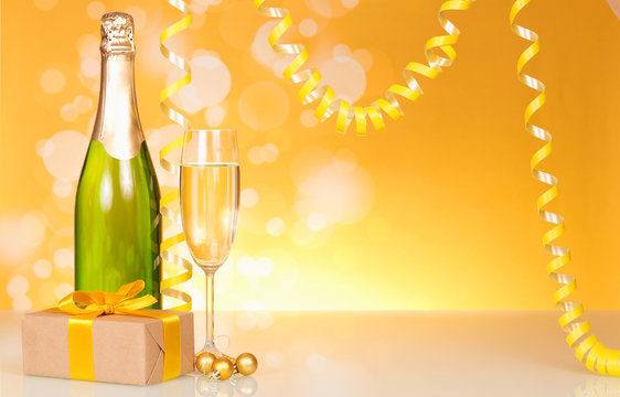 A bottle of champagne, a New Year's gift on a yellow shimmering background